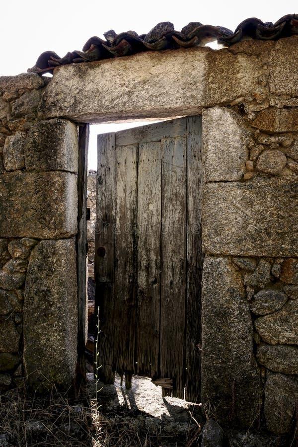 Vecchia porta di legno su una costruzione di pietra immagine stock libera da diritti