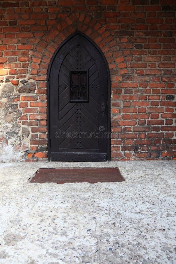 Vecchia porta di legno sul muro di mattoni di lerciume immagini stock
