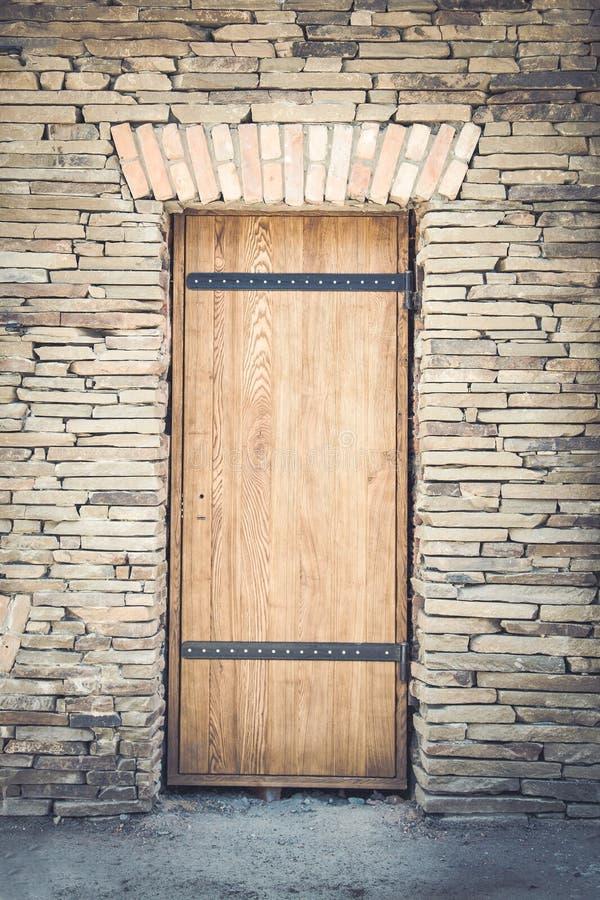 Vecchia porta di legno in una struttura del fondo della parte posteriore della parete di pietra immagine stock libera da diritti