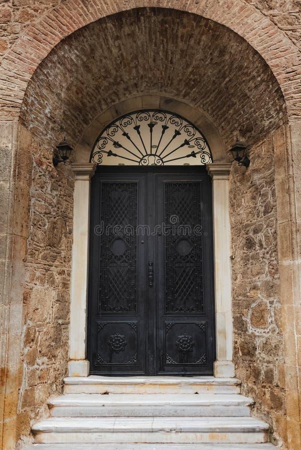 Vecchia porta di servizio in parete marrone Fotografia a colori verticale immagini stock