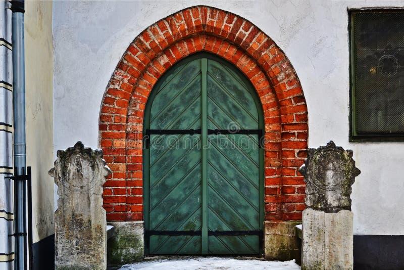 Vecchia porta verde di legno La casa dei tre fratelli a Riga latvia fotografie stock libere da diritti
