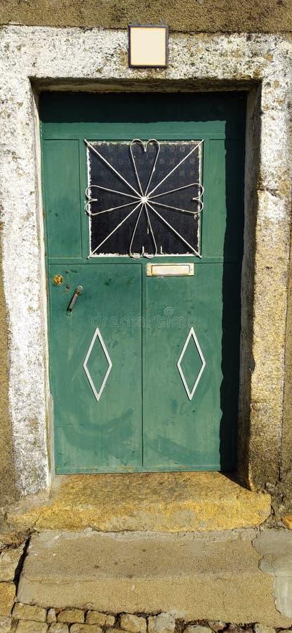 Vecchia porta verde metallica con la finestra immagini stock