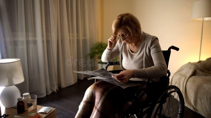 Vecchia prova femminile di leggere giornale in occhiali, problema dell'occhio, offuscamento della vista fotografia stock