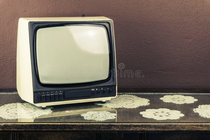 Vecchia retro TV sulla tavola d'annata, fondo marrone fotografia stock