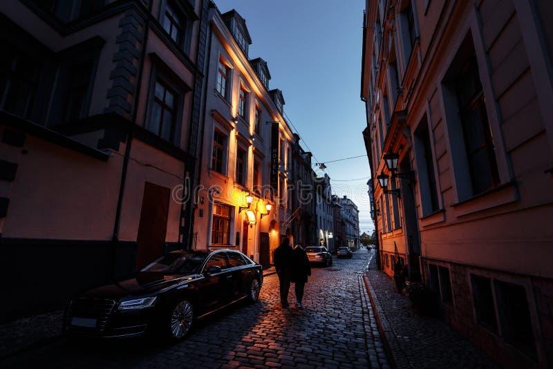 Vecchia Riga alla notte, Lettonia, Europa - la gente che cammina nell'le vie storiche della capitale europea immagine stock libera da diritti