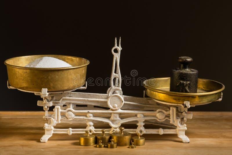 Vecchia scala d'annata bianca della cucina, ottone con i pesi e zucchero fotografie stock