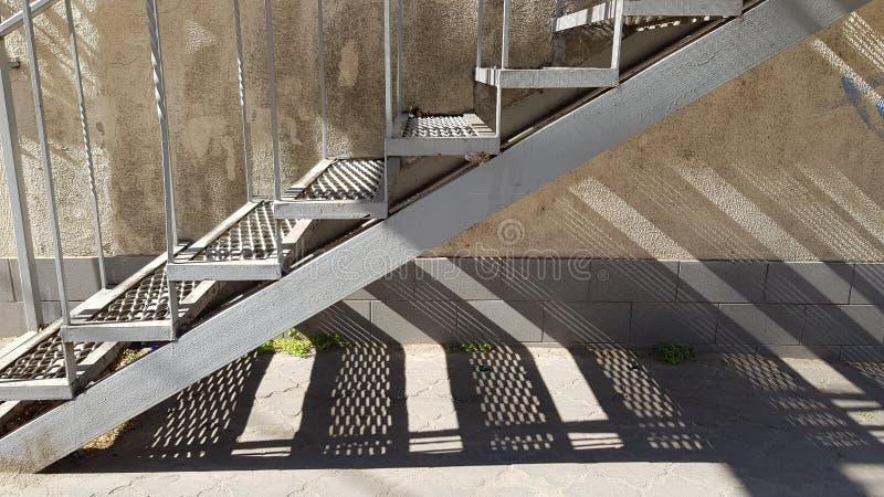 Vecchia scala del metallo con i punti della grata e le ombre a strisce geometriche sotto immagine stock