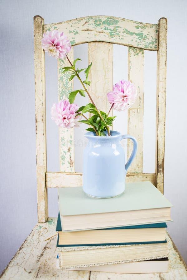 Vecchia sedia bianca con fondo, i fiori ed i libri bianchi immagini stock