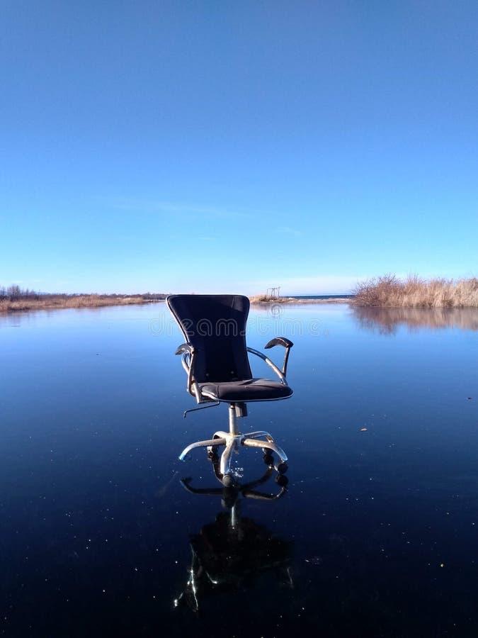 Vecchia sedia dall'ufficio su ghiaccio immagine stock