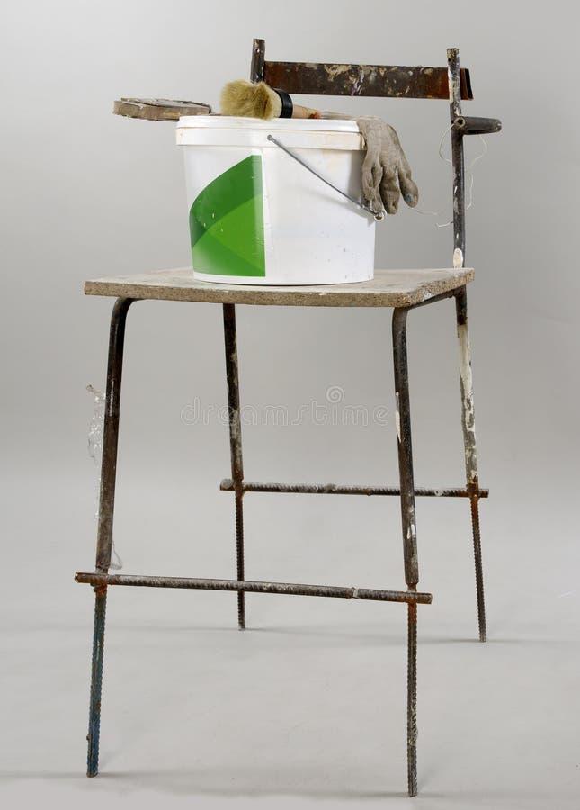 Vecchia sedia della costruzione e un secchio di pittura e una spazzola e un guanto fotografie stock libere da diritti