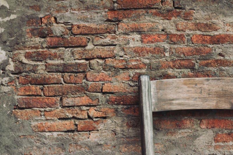 Vecchia sedia di legno nella costruzione abbandonata della parete immagini stock libere da diritti