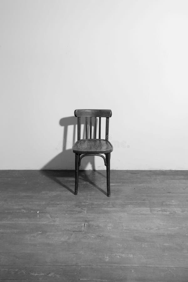 Vecchia sedia di legno in una stanza vuota immagini stock