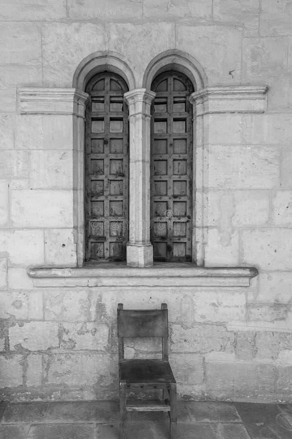 Vecchia sedia e Windows di scena antica del monastero in bianco e nero immagini stock