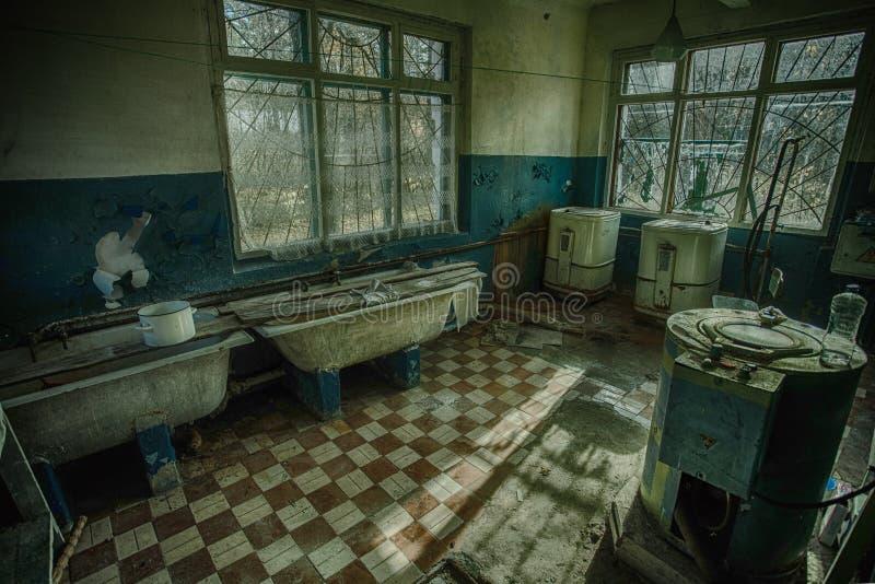 Vecchia stanza di lavanderia sinistra e terrificante in un ospedale psichiatrico abbandonato fotografia stock libera da diritti