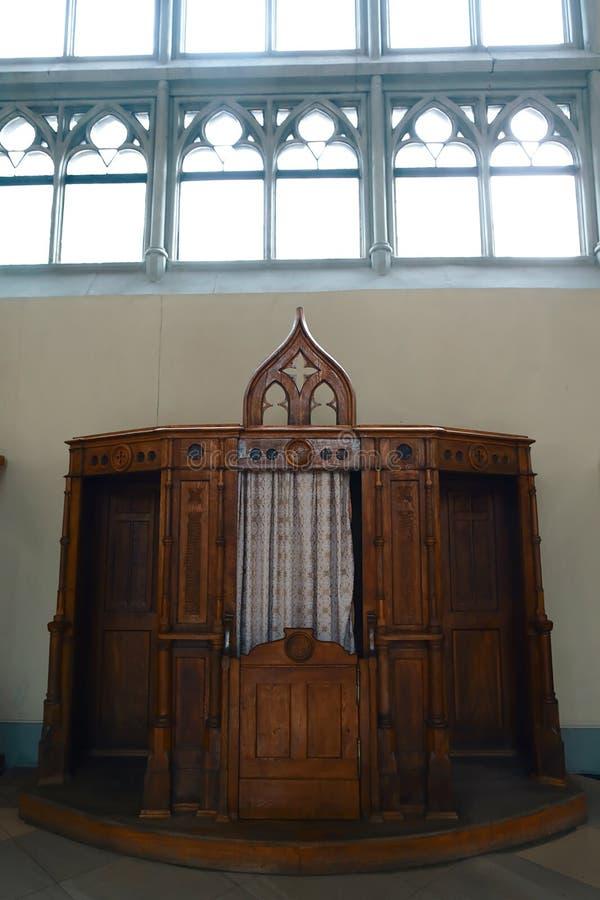 Vecchia, stanza di legno e confessionale che tiene segreto di una confessione, attributi del cristiano immagini stock