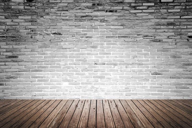 Vecchia stanza interna con il pavimento di legno e del muro di mattoni fotografia stock