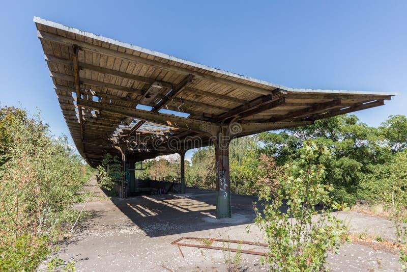 Vecchia stazione ferroviaria, abbandonata ed invasa - all'aperto con il tetto distrutto fotografie stock