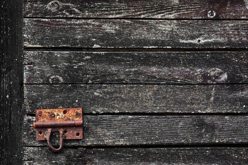 Vecchia struttura scura di legno di lerciume per fondo con il fermo di porta arrugginito immagine stock