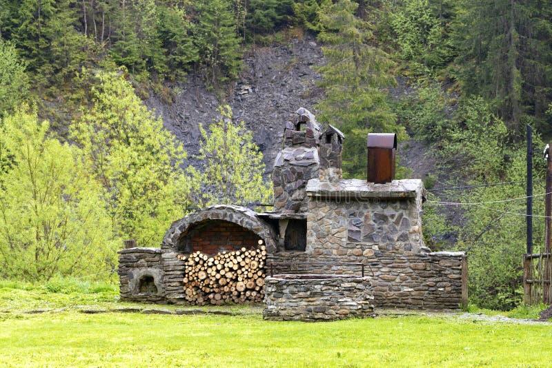 Vecchia stufa di pietra con legna da ardere e l'affumicatoio nelle montagne dei Carpathians fotografie stock libere da diritti