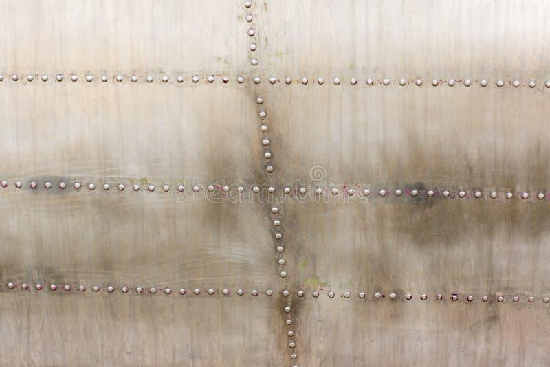 Vecchia superficie di metallo d'argento della fusoliera di aerei con i ribattini Piatto del ferro, struttura della lamiera di acc fotografie stock
