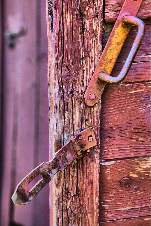 Vecchia superficie incrinata della porta del paese con la serratura del fermo del bullone del ferro e la d fotografia stock libera da diritti