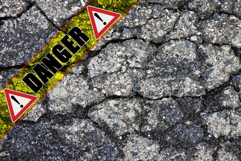 Vecchia superficie incrinata nociva pericolosa con la toppa - immagine della strada asfaltata di concetto con il testo del perico immagine stock