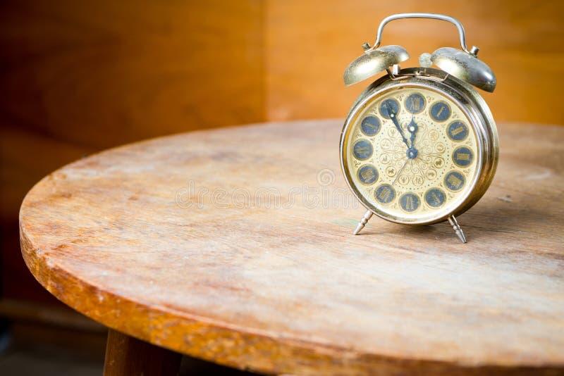 Vecchia sveglia utilizzata sulla tavola rotonda Tecnologia obsoleta ma grande progettazione - cinque - dodici immagine stock
