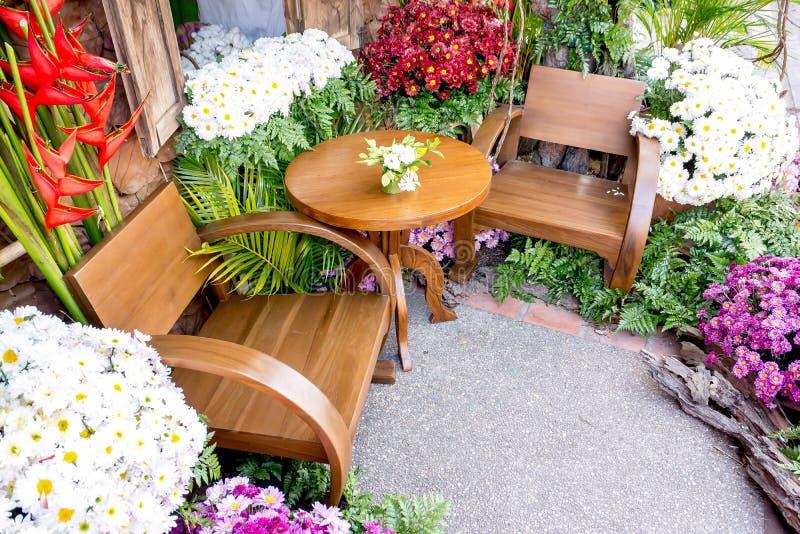 Vecchia tavola e sedie di legno circondate con il giardino di fiori, la tavola antica tailandese nordica e lo stile delle sedie immagini stock libere da diritti