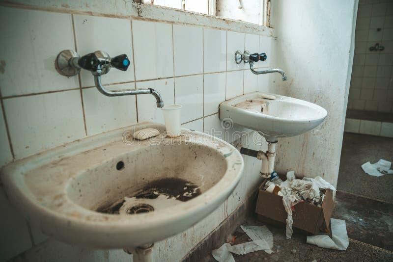 Vecchia toilette sporca nella costruzione abbandonata dell'ospedale psichiatrico sporcizia e disordine sull'attrezzatura sociale fotografie stock