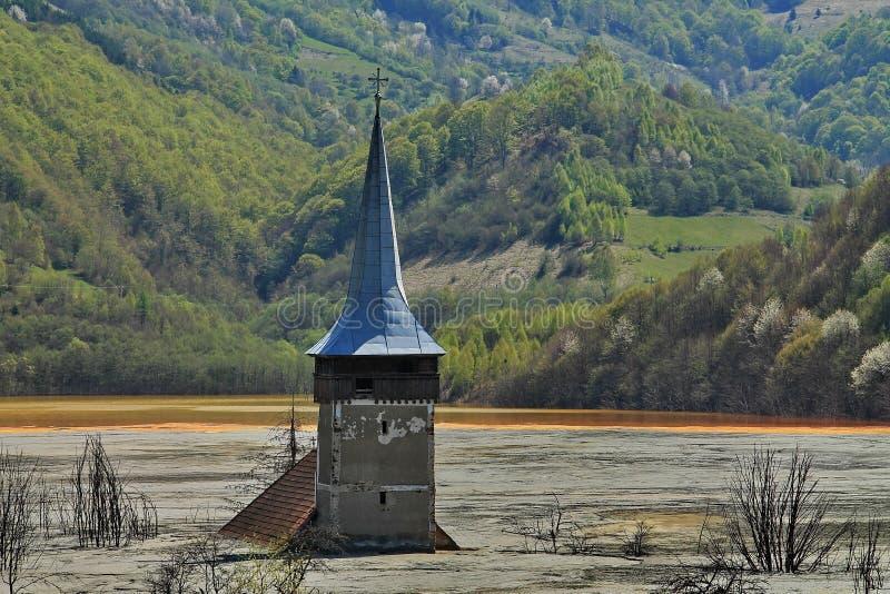 Vecchia torre di chiesa in lago contaminato fotografia stock