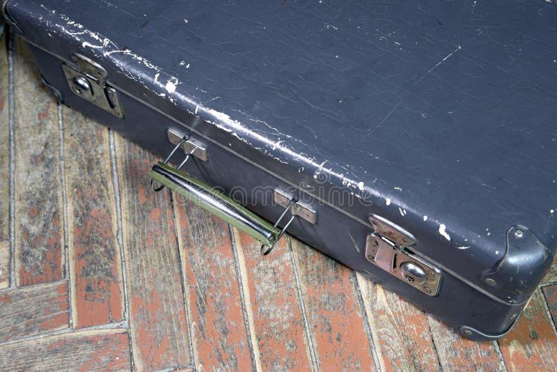 Vecchia valigia misera su un pavimento di legno fotografie stock