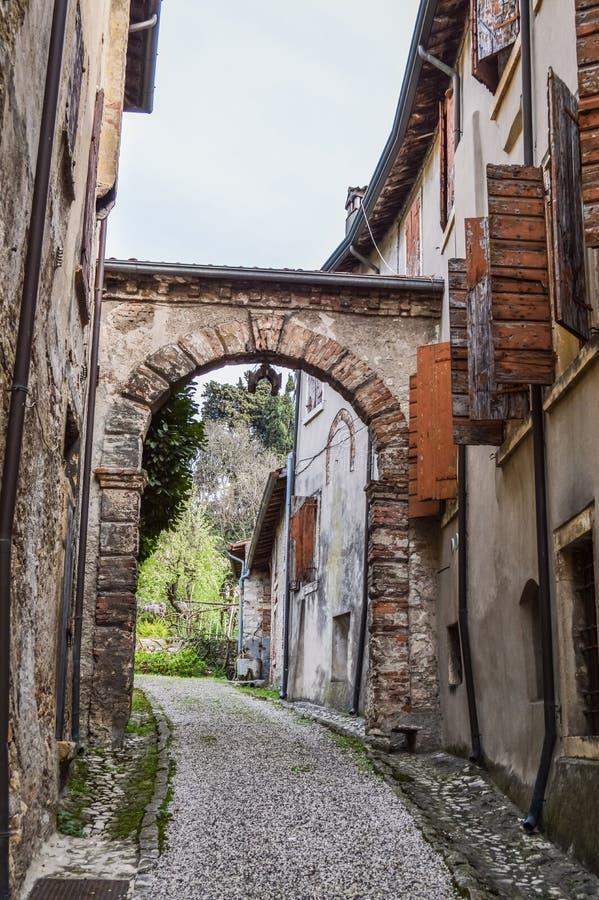 Vecchia via con l'arco nella città murata italiano antico di Soave fotografia stock libera da diritti