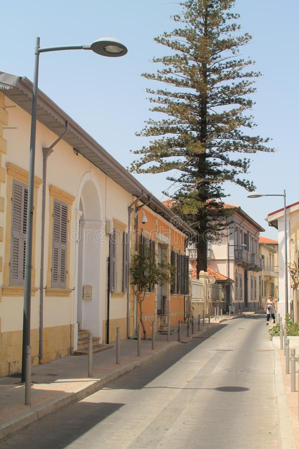 Vecchia via della città con le case tradizionali e l'albero alto fotografia stock libera da diritti