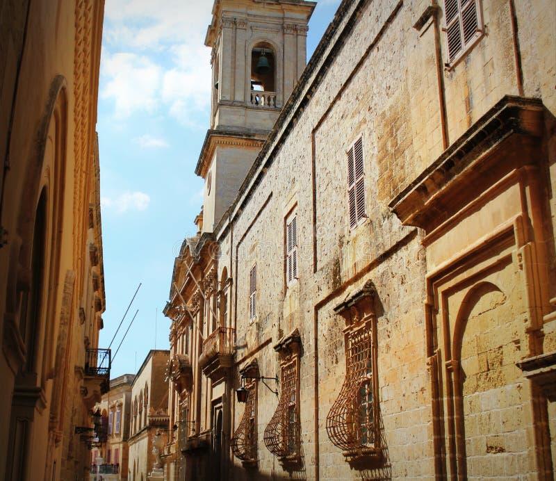 Vecchia via stretta di Mdina con il campanile Carmelitano della chiesa - Mdina, Malta fotografia stock