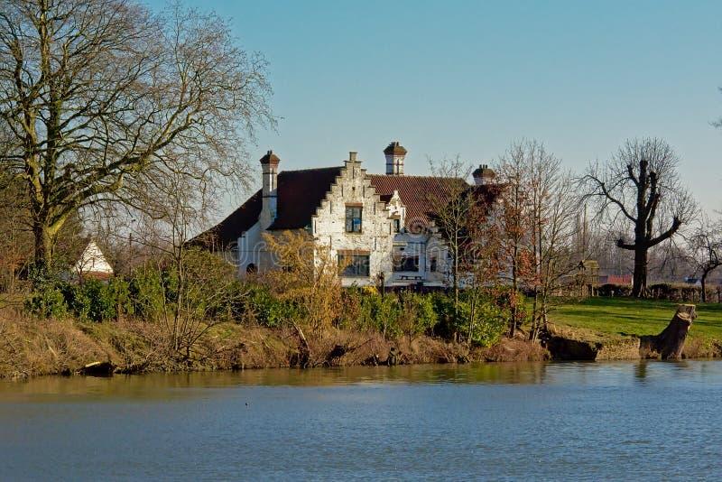 Vecchia villa bianca lungo il fiume Lys in Fiandre, Belgio immagine stock