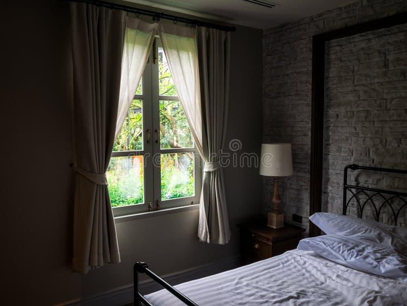 Vecchia vista del giardino di viallage della finestra nella stanza scura fotografie stock