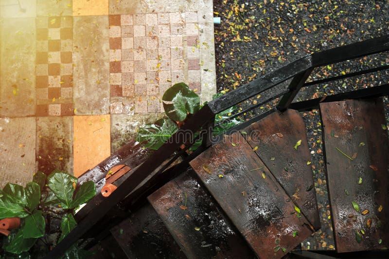 Vecchia vista di legno delle scale dalla vista superiore bagnata dalla pavimentazione delle mattonelle e della pioggia immagini stock