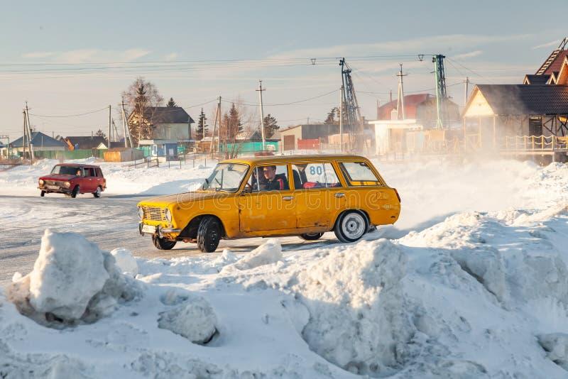 Vecchie automobili russe Lada per la corsa dell'azionamento sul ghiaccio su un lago congelato, lo spostamento e muoversi in uno s fotografie stock libere da diritti