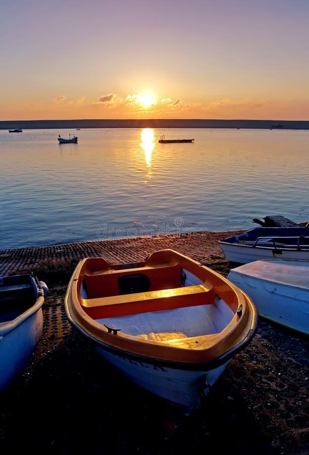 Vecchie barche di rematura dal tramonto del Sea During immagini stock