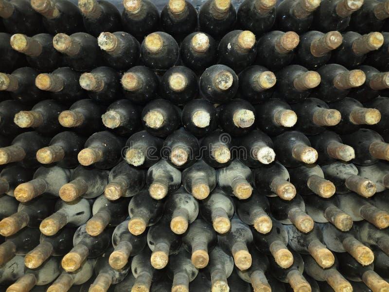 Vecchie bottiglie di vino sporche impilate su in cantina fotografia stock libera da diritti