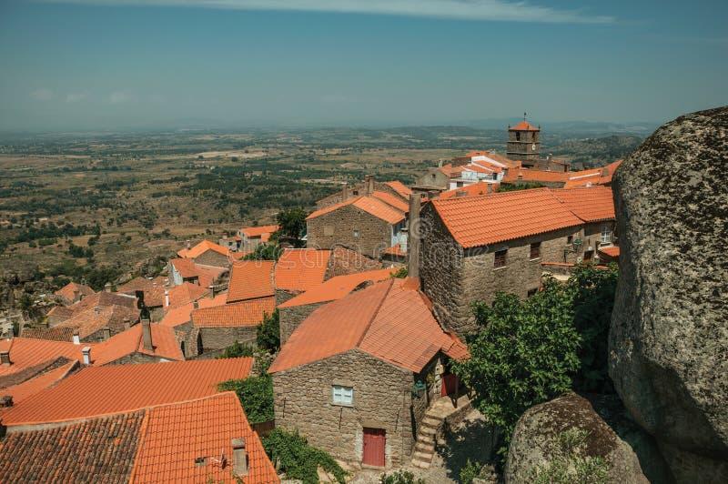 Vecchie case di pietra con il campanile della chiesa a Monsanto immagine stock