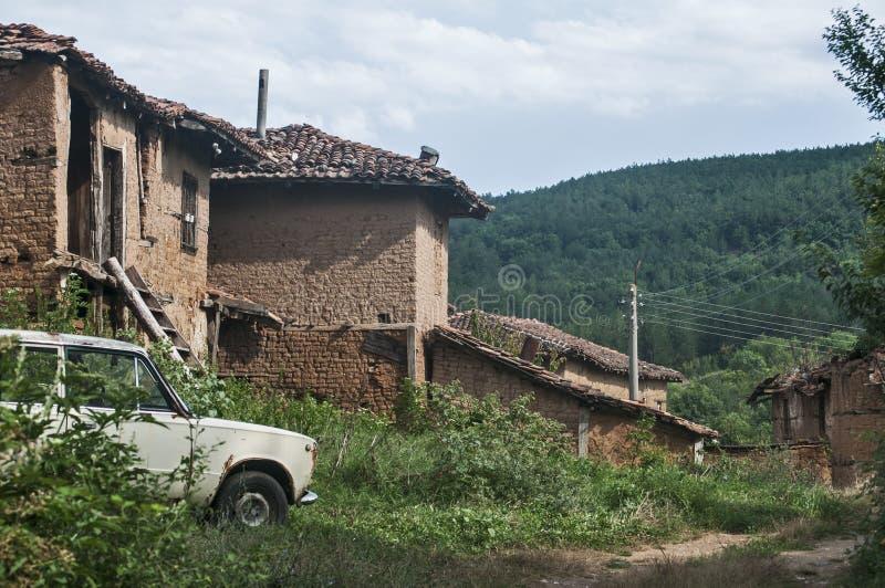 Vecchie case rurali ed automobile d'annata abbandonata fotografia stock libera da diritti