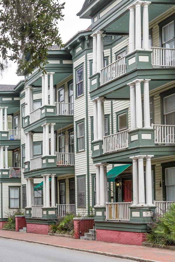 Vecchie case verdi e bianche con le colonne ed i balconi fotografia stock