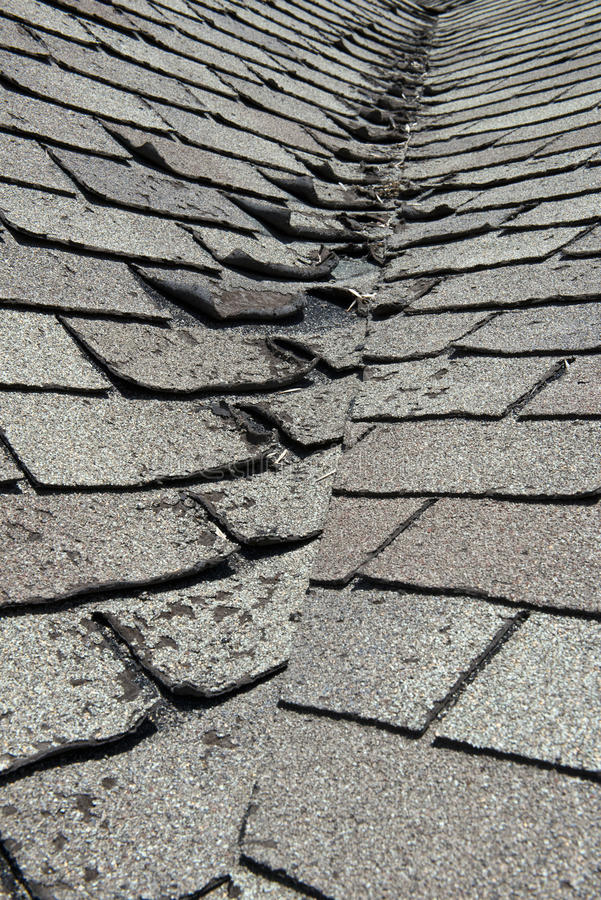 Vecchie cattive ed assicelle d'arricciature del tetto su una Camera o su una casa immagine stock
