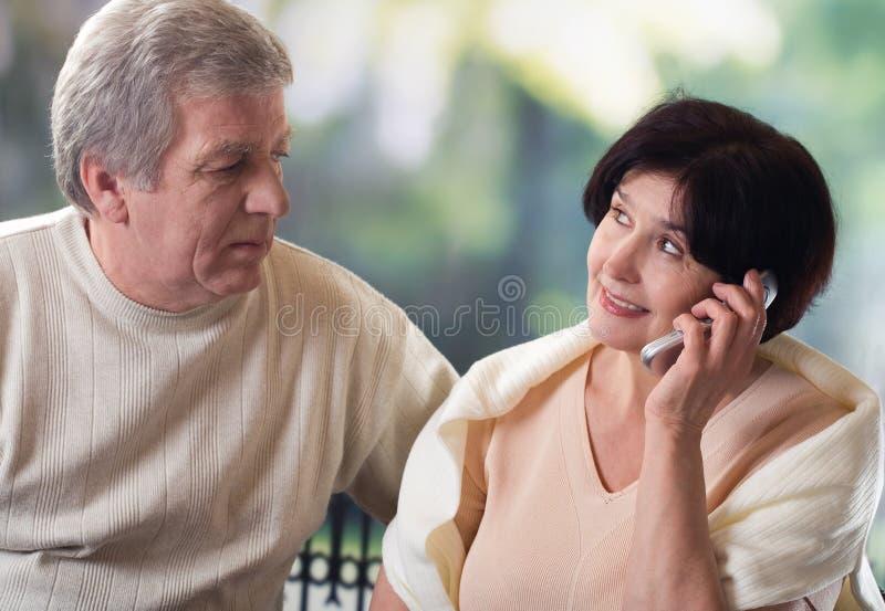 Vecchie coppie felici sul telefono mobile fotografie stock