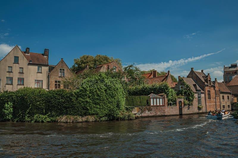 Vecchie costruzioni di mattone sul bordo del ` s del canale e sulla barca turistica in un giorno soleggiato a Bruges fotografia stock libera da diritti