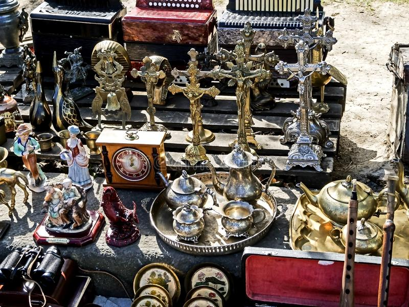 Vecchie figurine differenti del metallo, candelieri, piatti ed altre piccole cose sul mercato delle pulci immagine stock libera da diritti