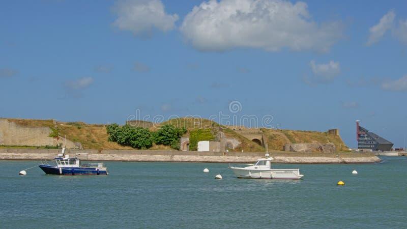 Vecchie fortificazioni, costruzione modoern e barche nel porto di Calais, Francia fotografia stock
