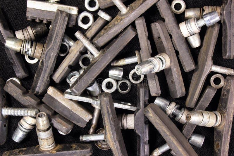 Vecchie ganasce del freno utilizzate ed indossate sporche della bicicletta con le rondelle ed il dado fotografia stock libera da diritti