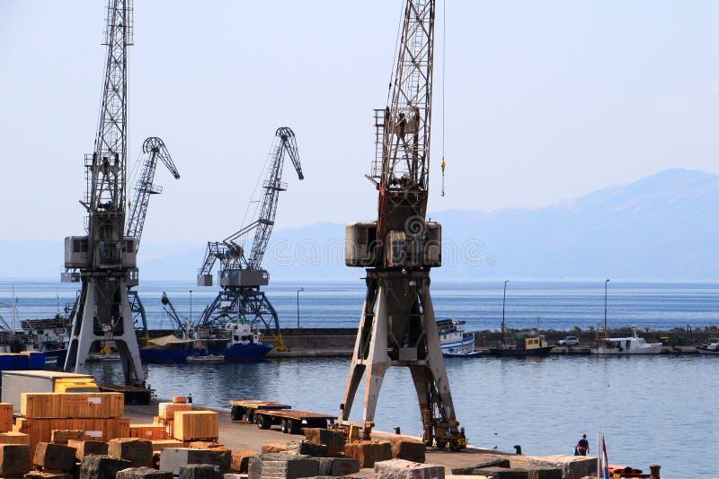 Vecchie gru grige del porto e piccole navi, porto di Rijeka, Croazia immagine stock libera da diritti